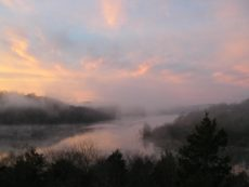 Dawn rising over a mist-shrouded Beaver Lake with multiple hues of pink, purple, blue, and the outline of the Ozark Mountains.