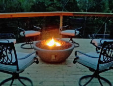 A warm flickering lava rock fire pit during twilight is surrounded by comfortable outdoor seating on the over sized lower Lake House deck with the lake and trees behind.