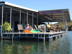 Two guests relax as they read books with fishing lines in the water on the spacious sun deck of our private dock.