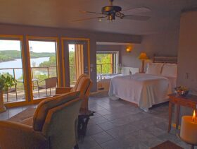 Recliners and a romantic candle in for ground with the queen-sized bed, Jacuzzi, and wall of windows overlooking Beaver Lake making up the background.