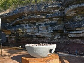 The bluff cabins's round, stone-facade, fire table on it's octagonal base with the 14' natural bluff in the background.