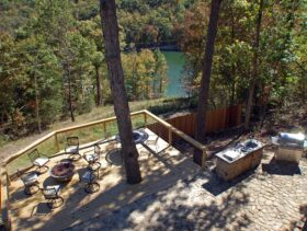 On a summer day looking from high above the expansive outdoor deck surrounded by trees has ample outdoor seating circling a lava rock fire pit as well as a large stone patio outdoor kitchen.