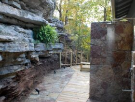 Sunlight reflects off the stream of water from the raindrop shower head on the Bluff Cabin's outdoor shower surrounded by natural limestone bluffs.