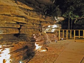 Mood lighting brings out features and shadows in the 14' tall natural bluff that forms one side of the private patio behind the Bluff Cabin.