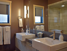 Looking into the stylish, modern bathroom with brushed, stainless steel fixtures, white overhanging sinks for two, gray cabinets with darker gray quartz counter-tops, and a large mirror for your convenience..
